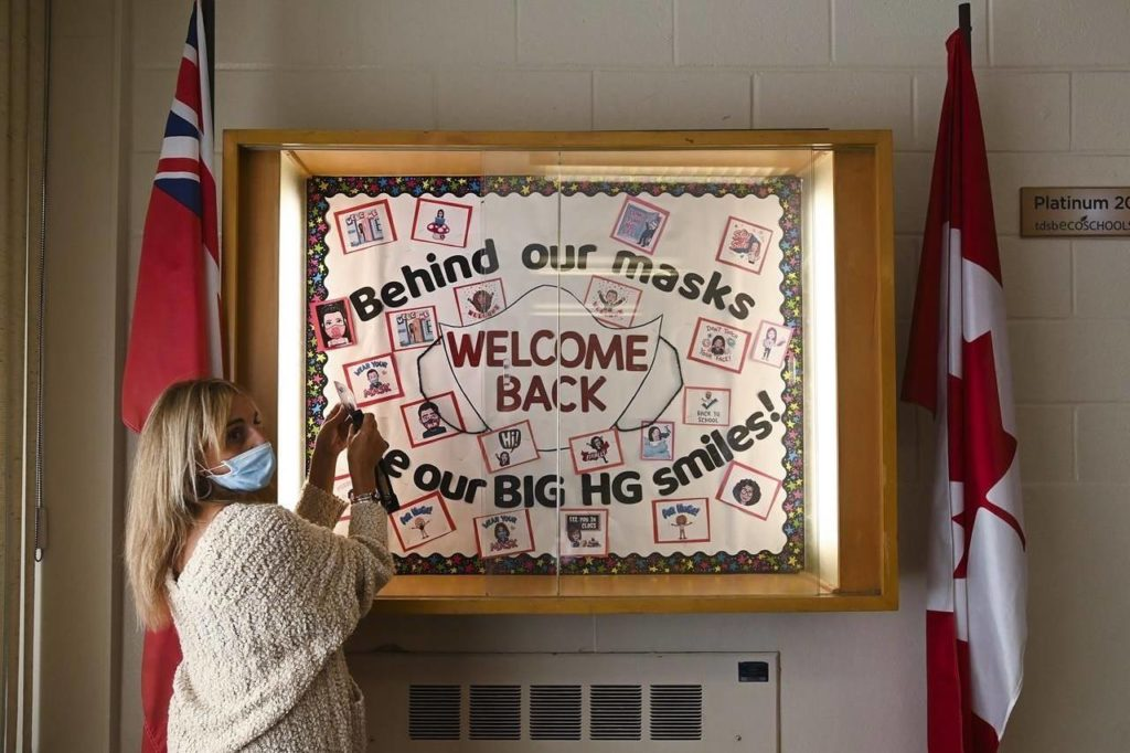 A teacher places the finishing touches on the welcome sign at Hunter's Glen Junior Public School which is part of the Toronto District School Board (TDSB) during the COVID-19 pandemic in Scarborough, Ont., on Sept. 14, 2020. THE CANADIAN PRESS/Nathan Denette