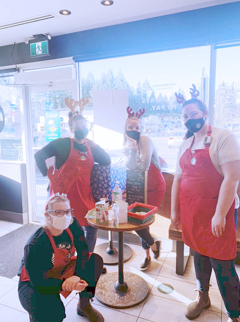 Staff at the Brookswood Starbucks at 200 Street and 40th Avenue, Samantha Robblin (kneeling) Sheryl Burk (L) Sonja Olsen (centre) and Sharla Thompson (R) posed Wednesday, Dec. 2, 2020, with the cards they were encouraging people to fill out for seniors isolated in care homes during the pandemic (Special to Langley Advance Times)