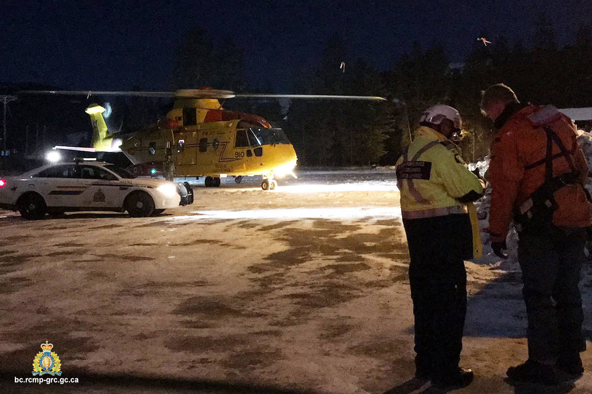 An RCMP officer confers with military rescuers outside their Cormorant helicopter near Bridesville, B.C. Tuesday, Dec. 1. Photo courtesy of RCMP Cpl. Jesse O'Donaghey