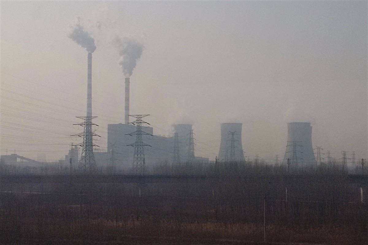 A coal-fired power plant seen through dense smog from the window of an electric bullet train south of Beijing, December 2016. China has continued to increase thermal coal production and power generation, adding to greenhouse gas emissions that are already the world's largest. (Tom Fletcher/Black Press)