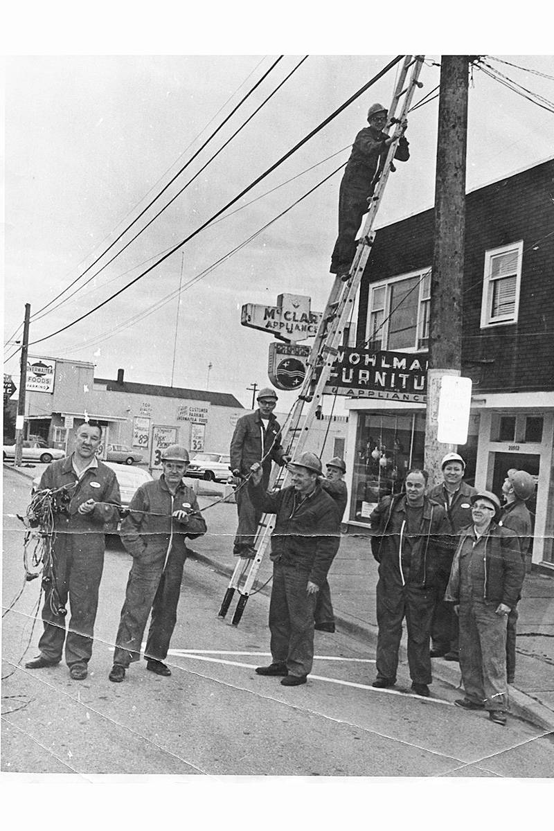 In the mid-1960s, Langley City volunteer firefighters strung Christmas lights downtown. The firefighters pictured are: bottom ladder Tony Slogar, top of the ladder Aksel Ebbeson, holding the ladder Maynard Brinnon, front row was Dick Sendall, Evan Young, Al Brown, John Anderson, John Stroyan, back row were, Merv Hunter and Terry Halsey. (Jim McGregor/Special to the Langley Advance Times)