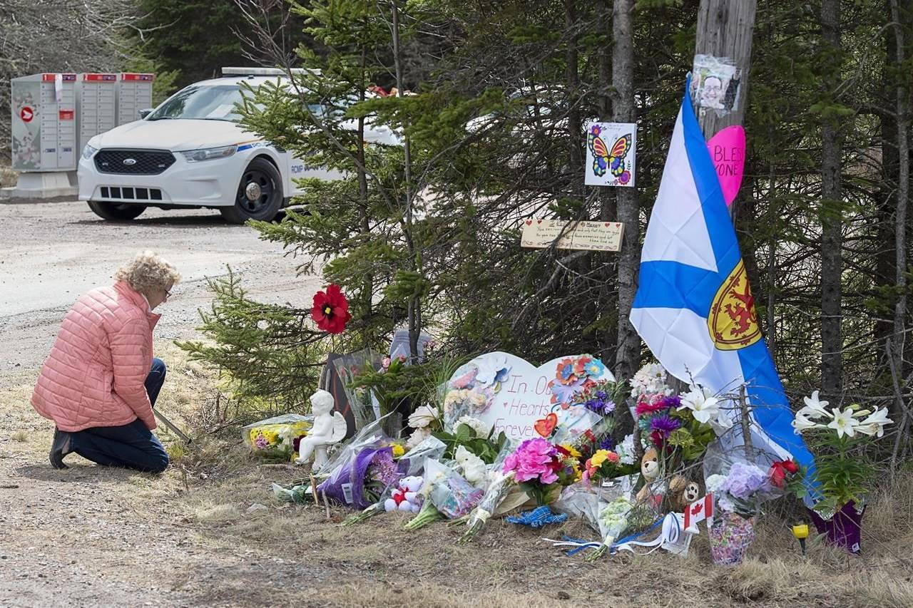 A woman pays her respects to victims of a mass shooting at a roadblock in Portapique, N.S. on Wednesday, April 22, 2020. THE CANADIAN PRESS/Andrew Vaughan