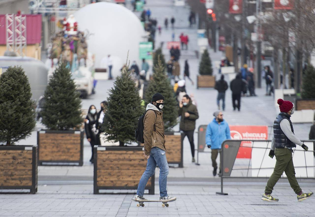 A man wears a face mask as he skateboards along a street in Montreal, Saturday, Dec. 5, 2020, as the COVID-19 pandemic continues in Canada and around the world. THE CANADIAN PRESS/Graham Hughes