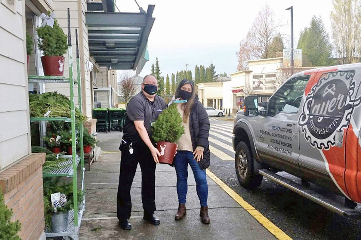 Save On Foods manager Cam Bates (L), seen here with Peterson Road PAC president Kristy Sayers, contributed gift cards and trees to the 2020 Peterson Road school food and Christmas hamper program (Special to Langley Advance Times)