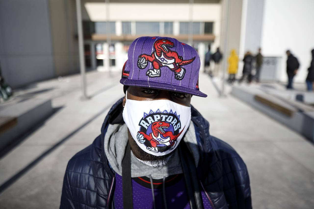 A shopper shows off his Toronto Raptors protective mask outside Vaughan Mills Shopping Centre in Vaughan, Ont., Sunday, Nov. 29, 2020. The Toronto Raptors say three members of the organization have tested positive for COVID-19. THE CANADIAN PRESS/ Cole Burston
