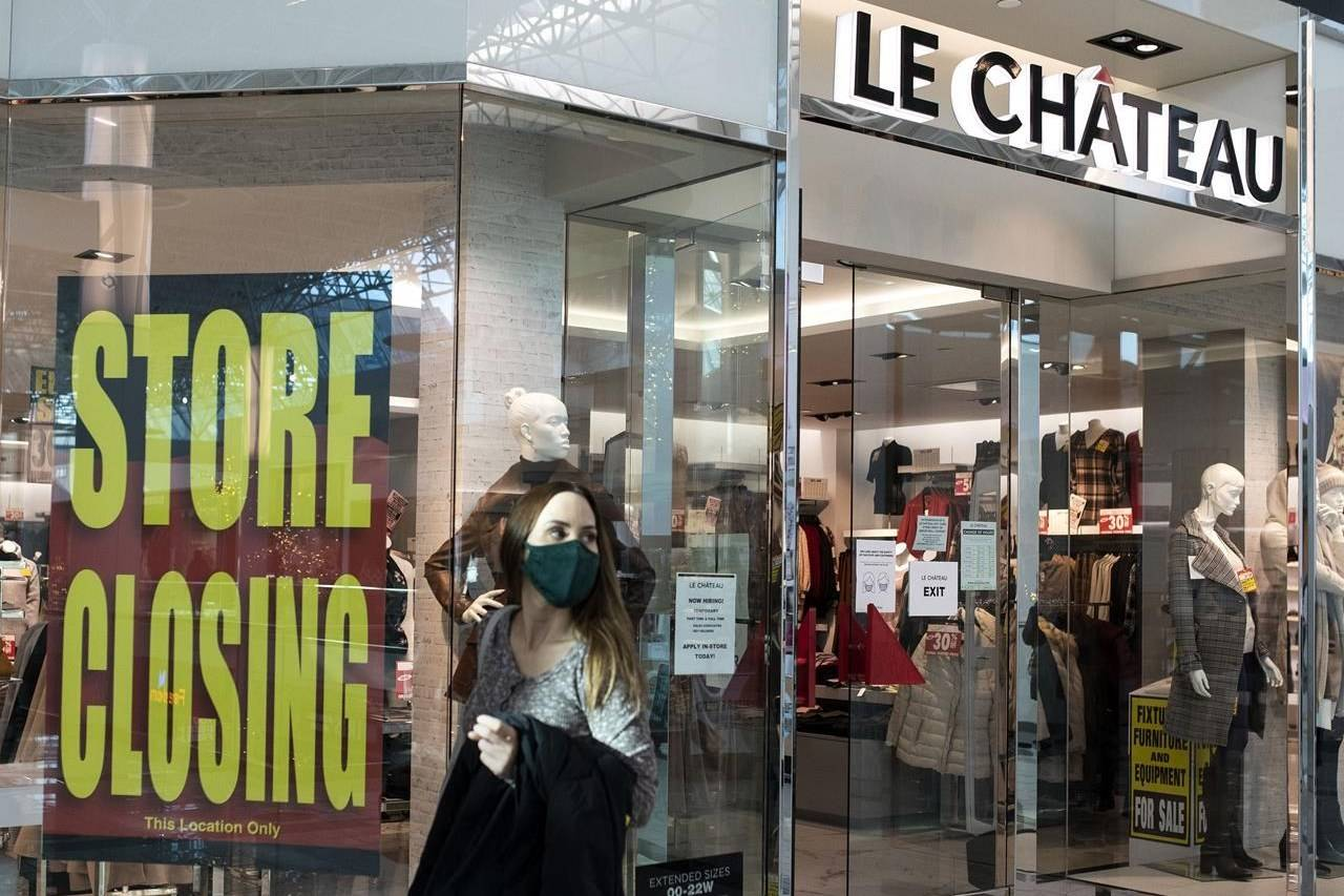 A woman in a face mask exits Le Chateau at Guildford Town Centre in Surrey, B.C., Friday, Dec. 4, 2020. The clothing store is going out of business amid the global COVID-19 pandemic. THE CANADIAN PRESS/Marissa Tiel