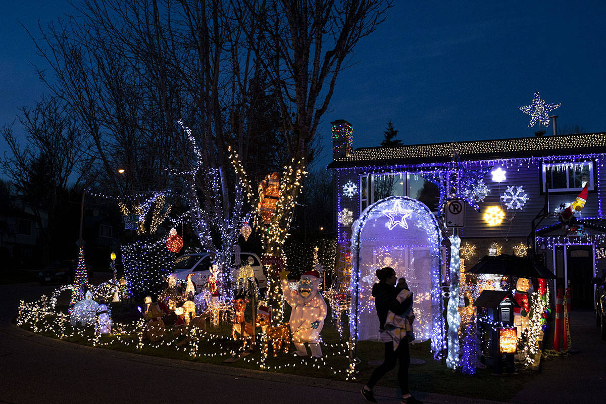 A woman holding a child walks past an elaborate Christmas lights display in Surrey, B.C. on Friday, Dec. 4, 2020. THE CANADIAN PRESS/Marissa Tiel