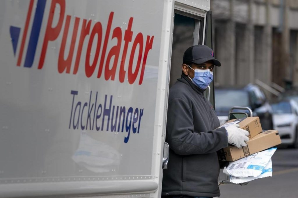 A Purolator driver wears a mask as he makes deliveries in Toronto, March 24, 2020. Purolator expects to deliver 46 million packages through its peak season this year, which runs through most of November and part of December, CEO John Ferguson said. THE CANADIAN PRESS/Frank Gunn