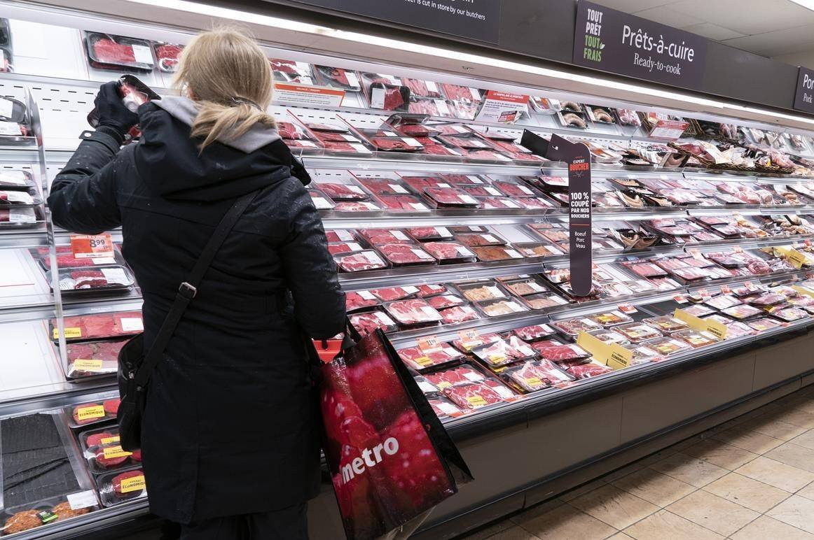 A customer shops at a meat counter in a grocery store in Montreal, on April 30, 2020. The average Canadian family will pay up to an extra $695 for food next year, as the pandemic, wildfires and changing consumer habits drive up grocery bills to the highest ever increase predicted by an annual food price report. THE CANADIAN PRESS/Paul Chiasson