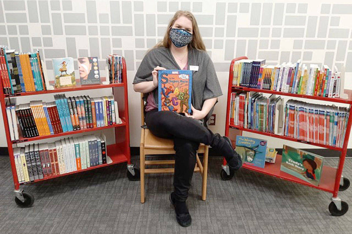 Emily Schlenker, with the City of Langley library, shows just a selection of books the Langley Literary Association purchased this 2020 season for kids helped by the local Christmas bureau. (Alicia Rempel/Special to Langley Advance Times)