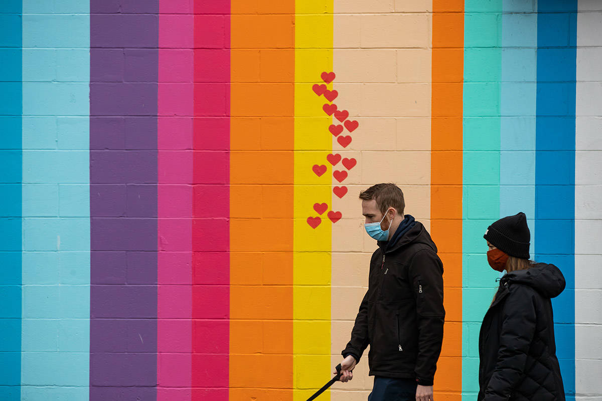 People wearing face masks to help curb the spread of COVID-19 walk past a multi-colour mural with hearts painted on it, in Vancouver, on Sunday, November 22, 2020. The use of masks is mandatory in indoor public and retail spaces in the province. THE CANADIAN PRESS/Darryl Dyck