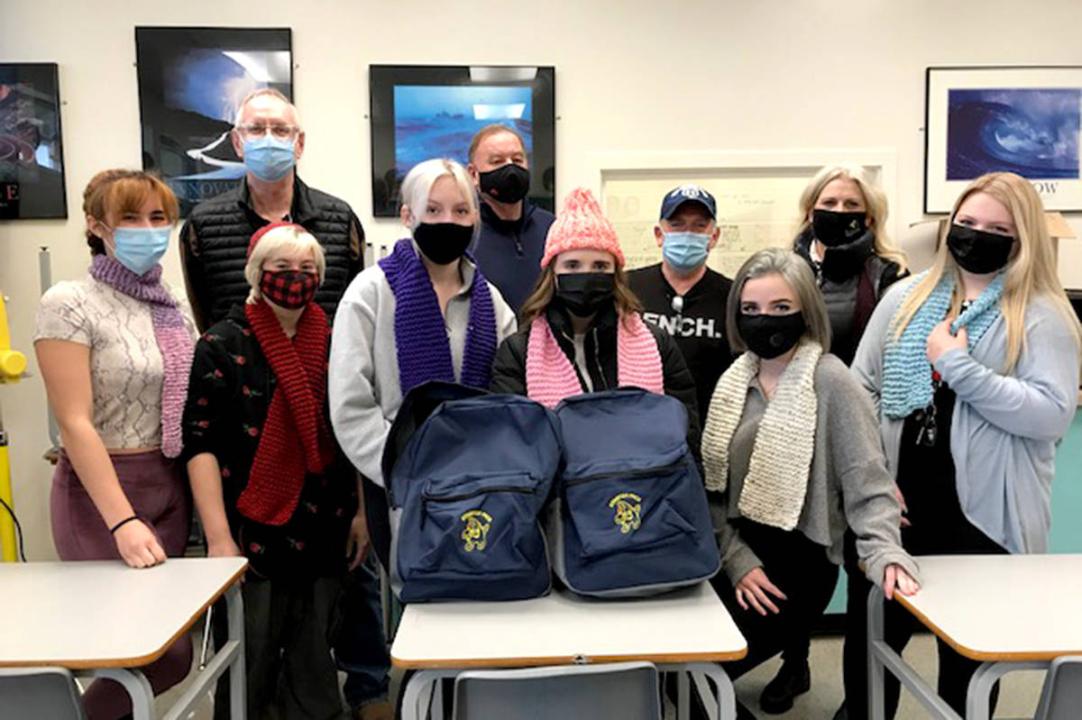 Rotarians Charlie Fox, George Bryce, Rob Robinson, and Lara Petrie join the ACSS Hairdressing students modelling the specially-made toques and scarves as they prepare this week's Starfish backpacks. (Pauline Buck/Special to the Aldergrove Star)