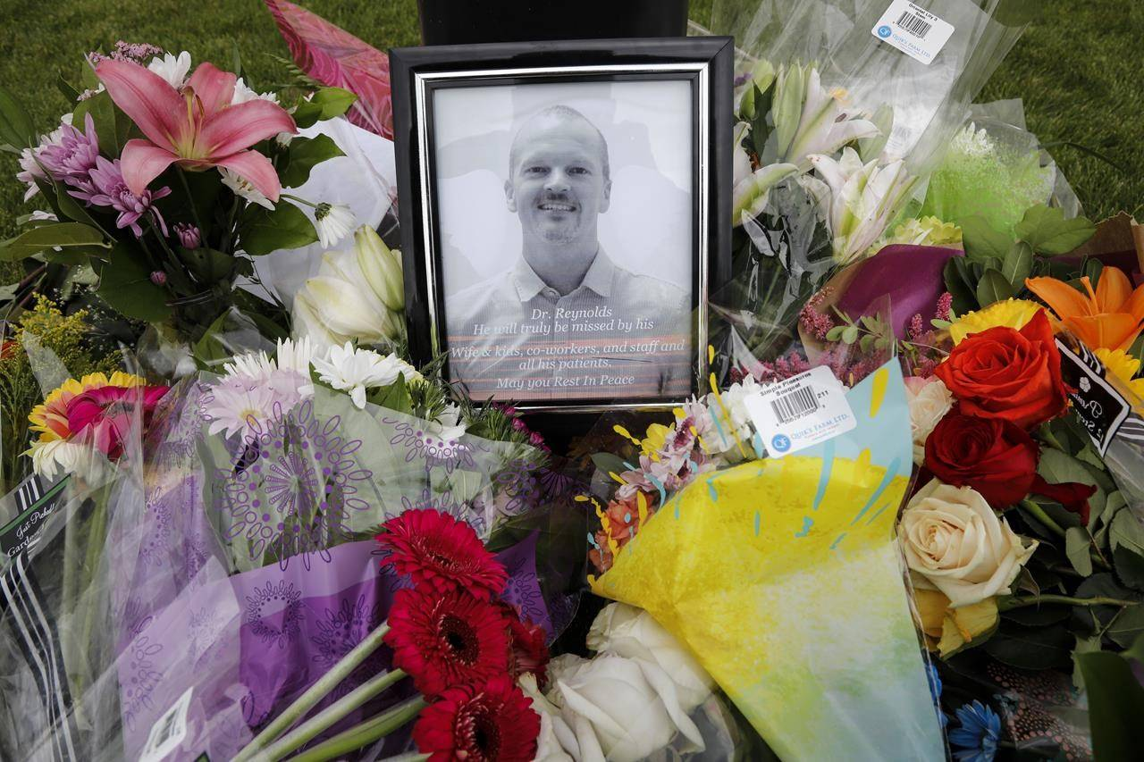 An impromptu memorial for Dr. Walter Reynolds, who died after he was attacked in an examination room, rests outside the Village Mall walk-in clinic in Red Deer, Alta., on Aug. 11. Deng Mabiour pleaded not guilty to first-degree murder in court on Monday. (File photo by The Canadian Press)