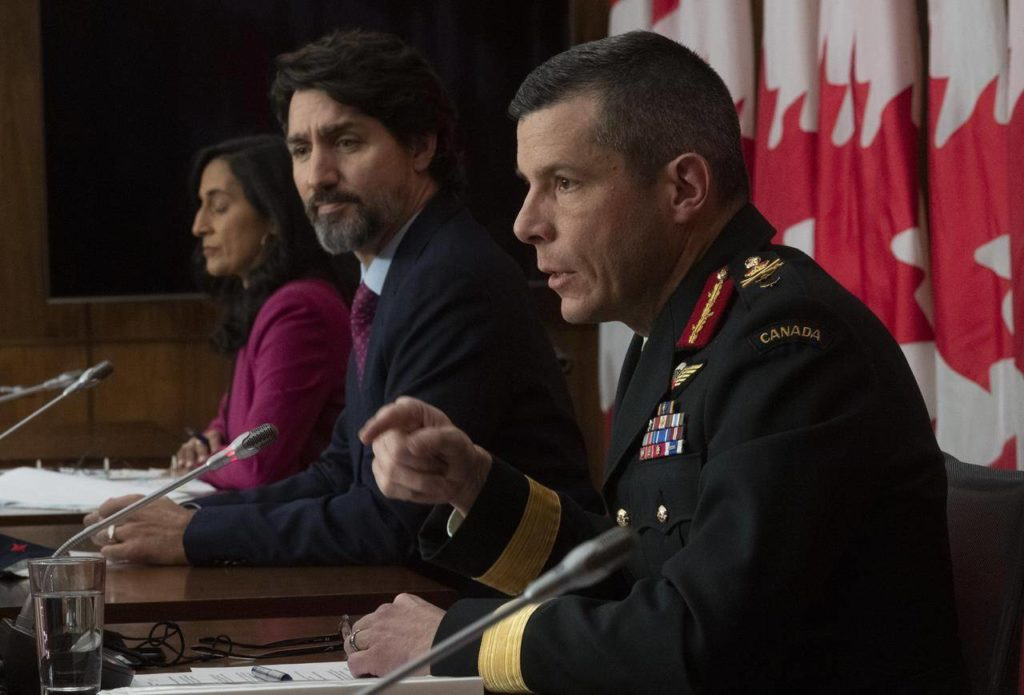 Public Services and Procurement Minister Anita Anand and Prime Minister Justin Trudeau listen to Major General Dany Fortin respond to a question during a news conference in Ottawa, Monday, Dec. 7, 2020. THE CANADIAN PRESS/Adrian Wyld