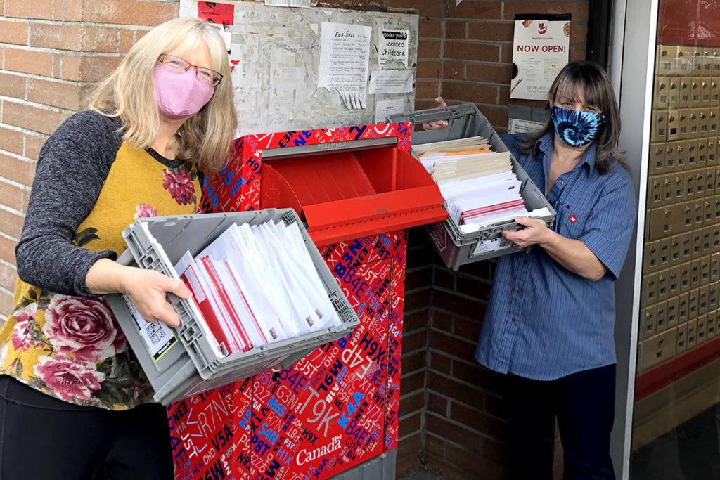 Karen Long gives Bonnie from the Aldergrove post office 360 Christmas cards from local students to Aldergrove Legion members over the age of 70. (Special to the Aldergrove Star)