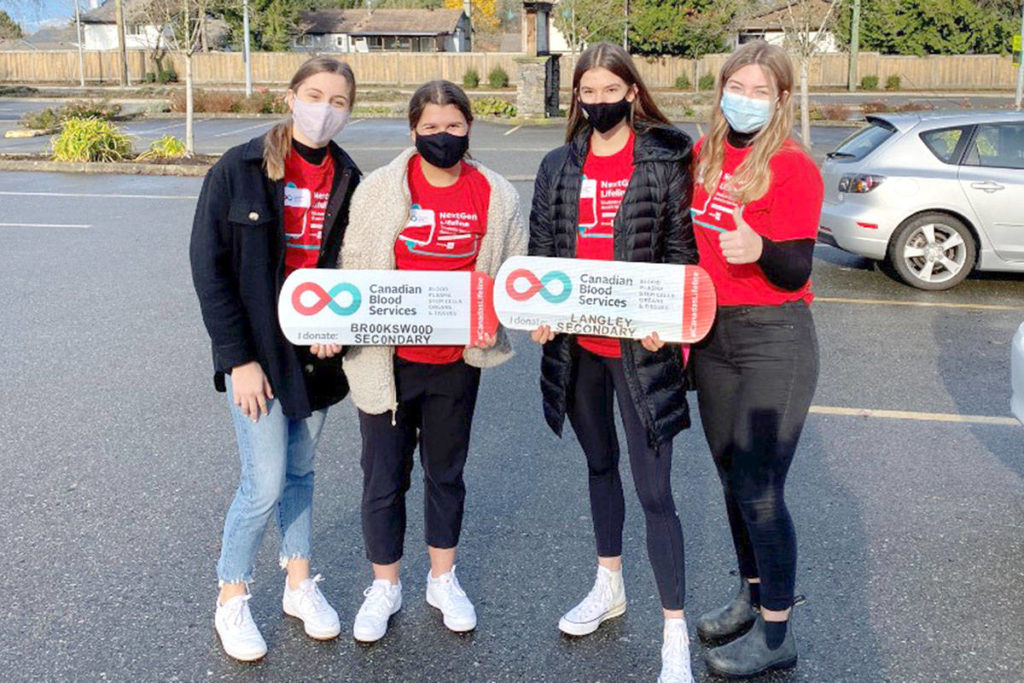 Grade 12 students Stefanie Robb and Kate Straforelli from Brookswood Secondary, and Mya Ellis and Cassie Renaud from Langley Secondary schools organize a community blood drive on Dec. 17, 2020 at Church in the Valley. (Canada Blood Services/Special to Langley Advance Times)
