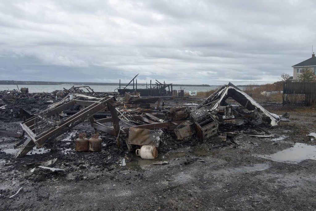 Debris from a burnt out fish plant is scattered along the shore in Middle West Pubnico, N.S. on Saturday, Oct. 17, 2020. The Nova Scotia RCMP confirmed today they have arrested 21 people as they continue to investigate a violent confrontation at a lobster pound at the centre of a dispute over a self-regulated Indigenous lobster fishery. THE CANADIAN PRESS /Andrew Vaughan