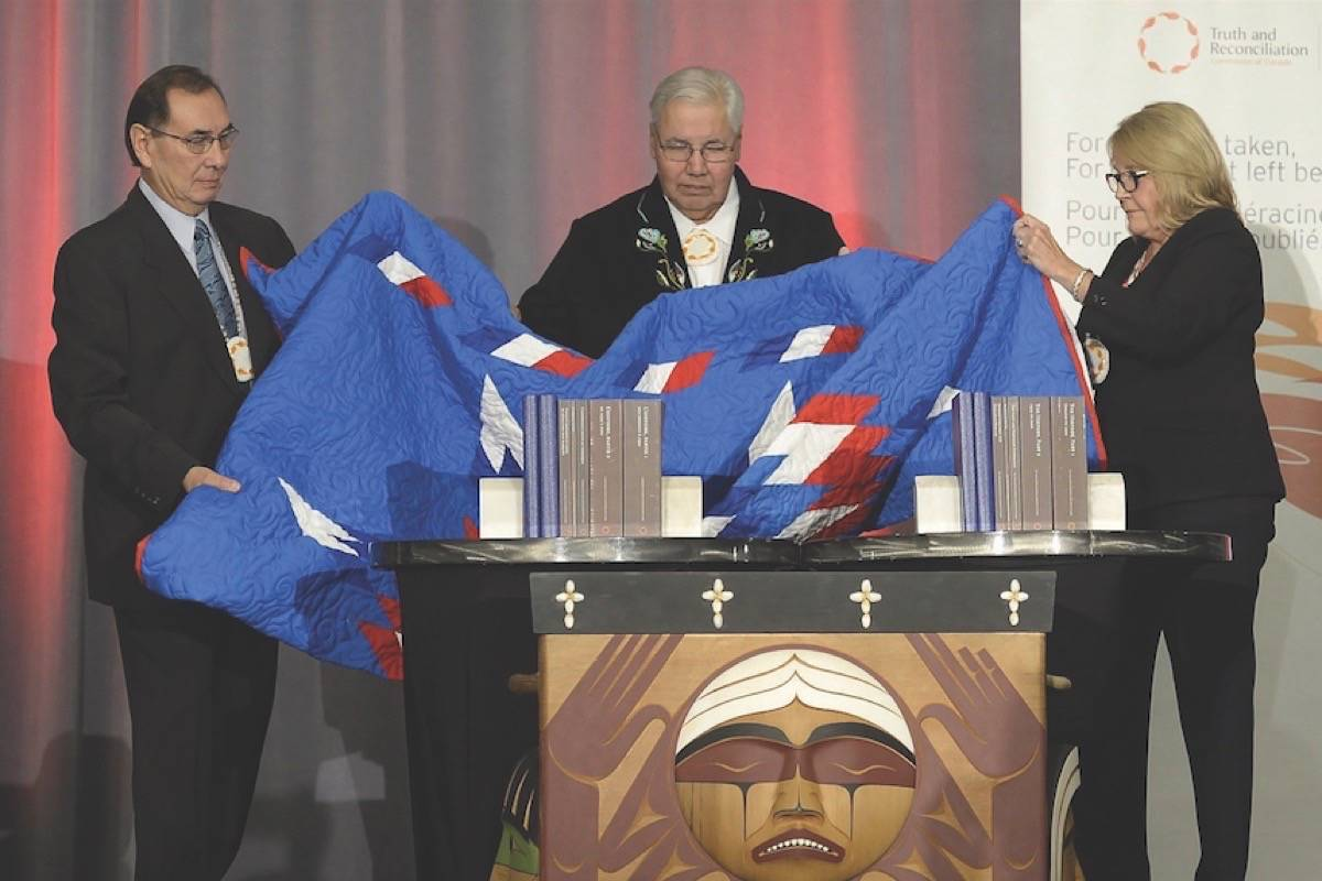 In this file photo, Justice Murray Sinclair (centre) and Commissioners Chief Wilton Littlechild (left) and Marie Wilson pull back a blanket to unveil the Final Report of the Truth and Reconciliation Commission of Canada on the history of Canada's residential school system, in Ottawa on Tuesday, Dec. 15, 2015. THE CANADIAN PRESS/Adrian Wyld