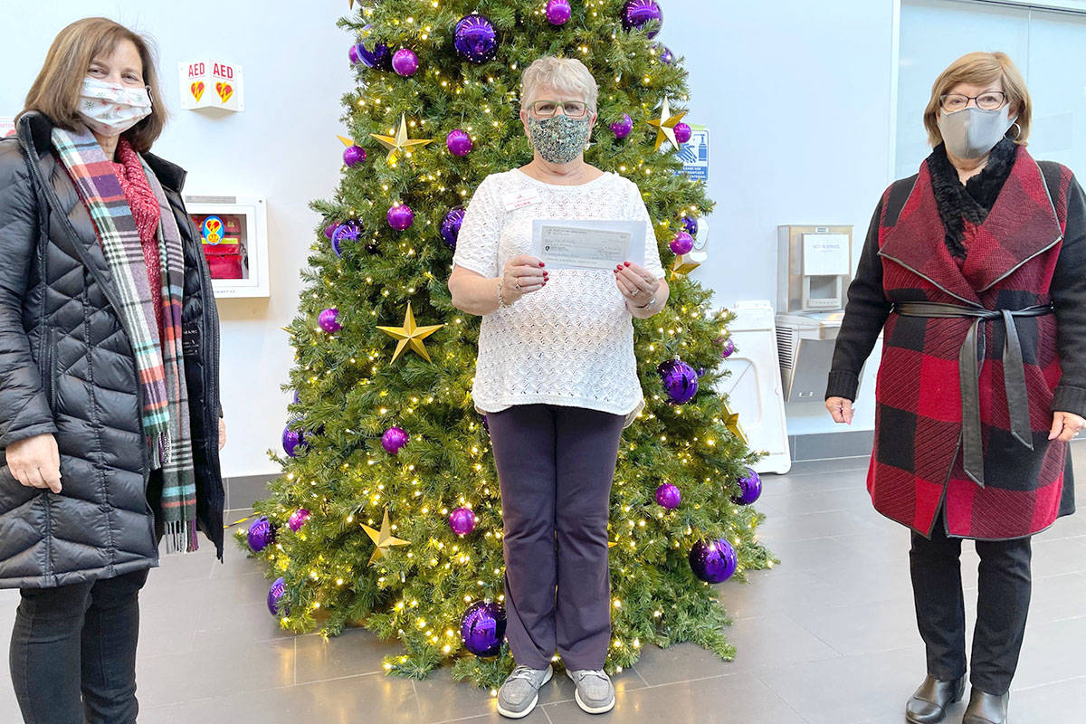 On Saturday, Dec. 12, 2020, Grace Stewart and Charlene Fassbender from the Thank-you for Caring Society visited the Langley Christmas Bureau's temporary location at Timms Community Centre to present bureau coordinator Velma MacAllister (centre) with a cheque for more than $30,000. (Peter Fassbender/Special to Langley Advance Times)