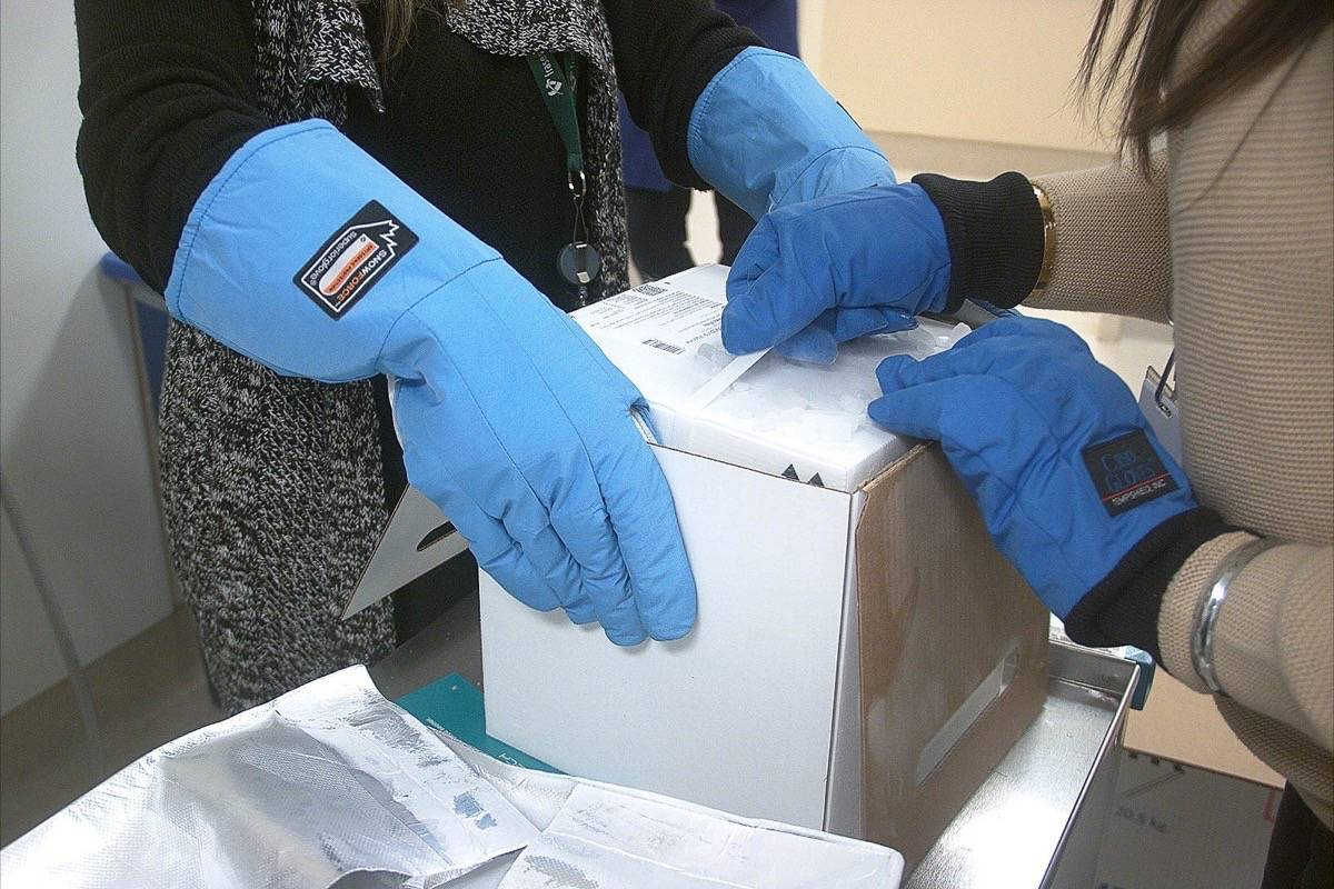 Public health workers unpack B.C.'s first shipment of Pfizer vaccine against COVID-19, which has to be kept in low-temperature packaging until administering, Dec. 13, 2020. (B.C. government)