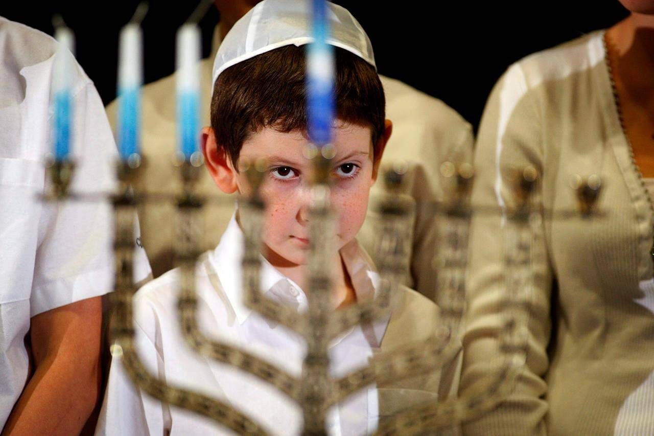 A young boy looks through the menorah during a lighting ceremony at the Calgary Jewish Community Centre on Thursday, Dec. 22, 2011. COVID-19 is prompting Jews to find creative ways to safely celebrate Hanukkah this year. THE CANADIAN PRESS/Jeff McIntosh