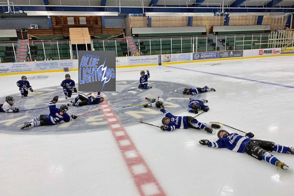 Members of the Blue Lightning team sprawled on the ice at George Preston arena at the end of a skate-a-thon that raised close to $2,000 for the Langley Christmas Bureau (David Haugen/special to Langley Advance Times)