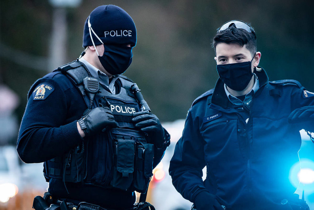 RCMP officers wearing face masks to curb the spread of COVID-19 stand by as protesters opposed to the Trans Mountain pipeline expansion block rail lines, in Burnaby, B.C., on Friday, November 27, 2020. THE CANADIAN PRESS/Darryl Dyck
