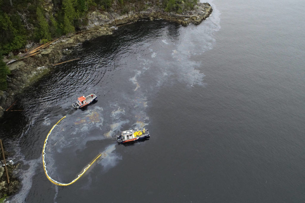 The on-site team deploys a boom curtain to contain the oil spill near Nootka Island. (Unified Command)
