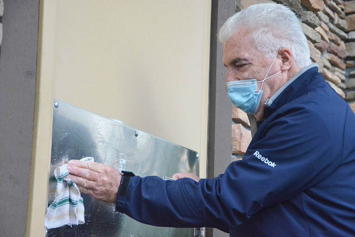 Art Mossop, who lives in a condo near 207A Street and 82nd Avenue, cleaned off a graffiti tag on Thursday, Dec. 17. The vandal left almost 30 tags inside and outside of local buildings in one night. (Matthew Claxton/Langley Advance Times)