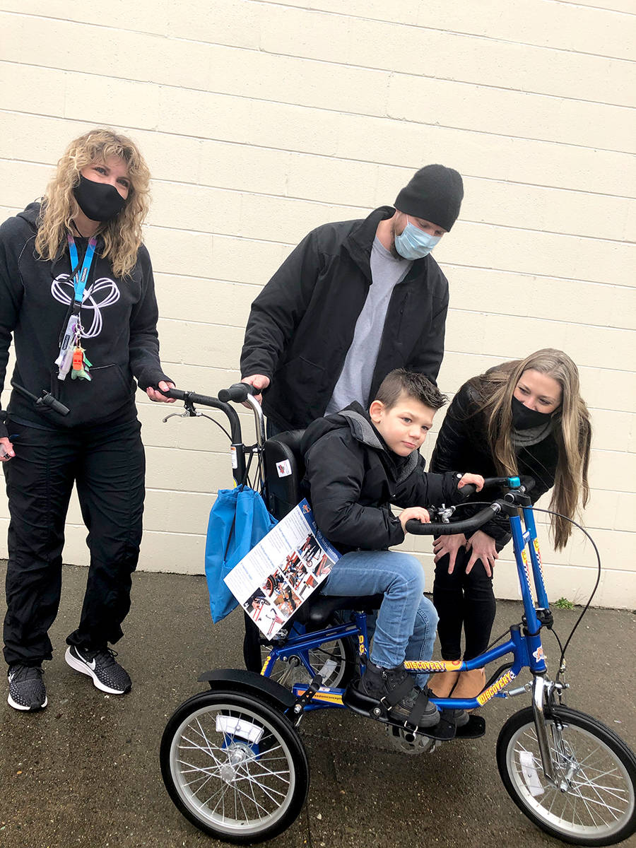 Heath McKenzie from Cranky's Bike Shop delivered a Christmas gift to Lennox Unruh, a Grade 2 student with different abilities at Coghlan Fundamental Elementary. (Special to the Star)