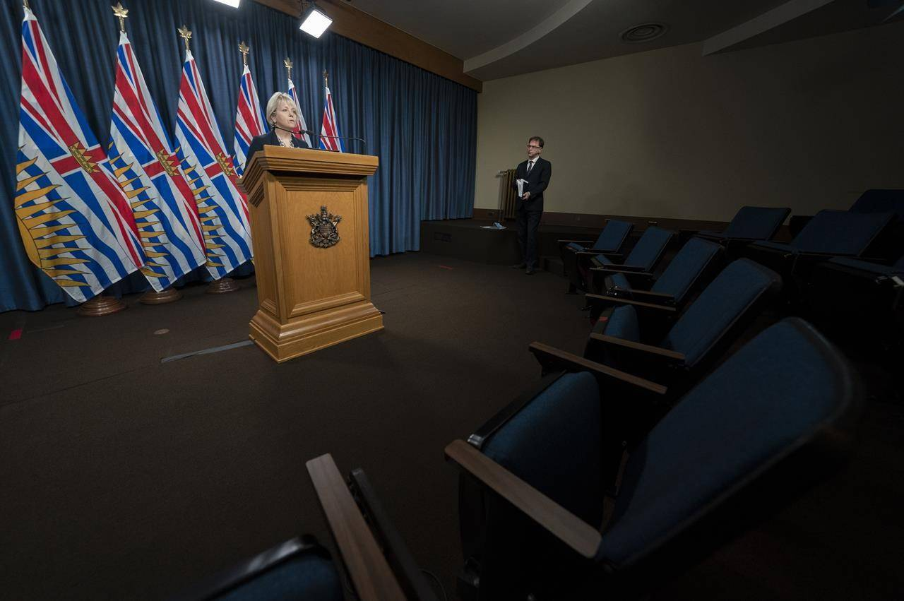 Health Minister Adrian Dix looks on as Dr. Bonnie Henry gives her daily media briefing regarding COVID-19 for the province of British Columbia in Victoria, B.C., Monday, December 7, 2020. (THE CANADIAN PRESS/Jonathan Hayward)