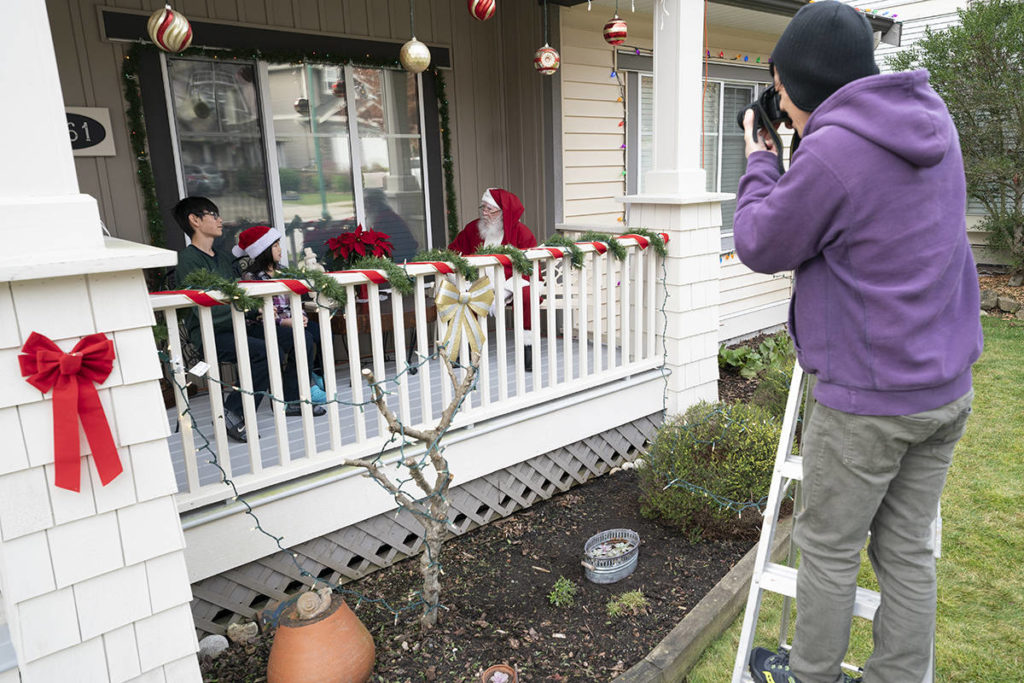 Takuo Nakanishi takes a physically distanced photo of his children Soyoka and Arata with a Santa wearing a protective face mask to help prevent the spread of COVID-19, in Abbotsford, B.C, Sunday, Dec. 6, 2020. THE CANADIAN PRESS/Jonathan Hayward