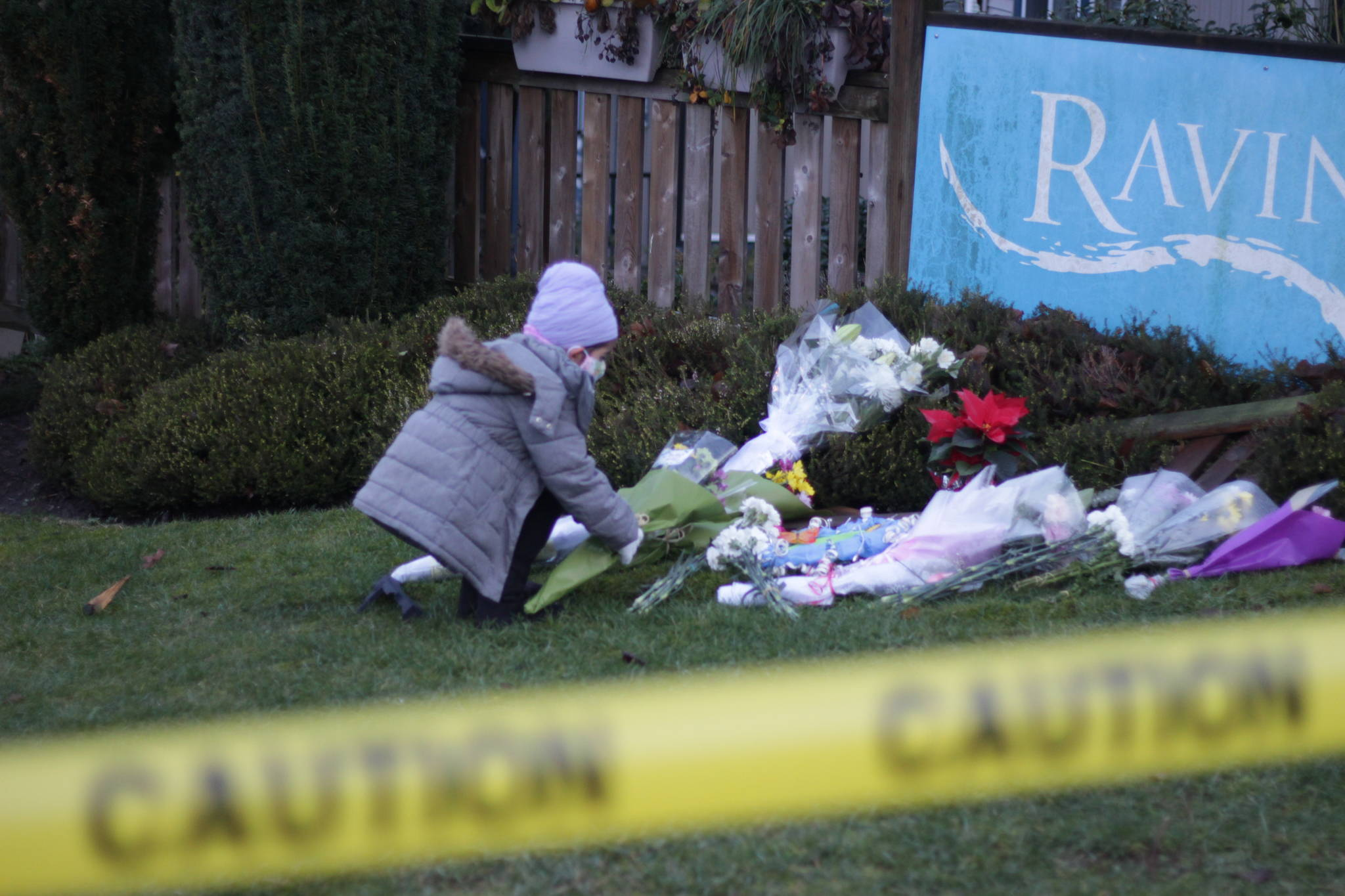A child in the community places flowers at the site where a Surrey mom was killed by a runaway cargo van on Tuesday, Dec. 15, 2020. On Thursday, dozens of people from the community came together to pay tribute to the mom. (Photo: Lauren Collins)