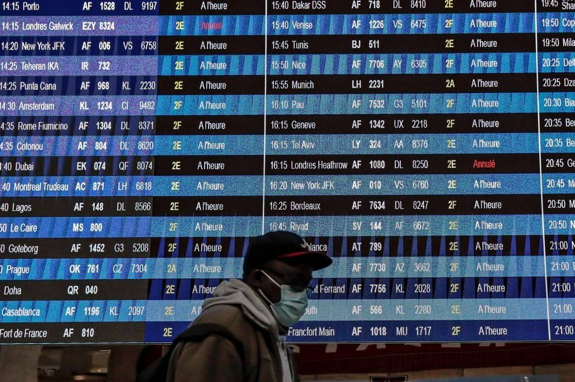 Passenger wearing a face mask walk past a flight information board at Paris' Charles de Gaulle international airport in Roissy, Monday Dec. 21, 2020. France is banning all travel from the U.K. for 48 hours in an attempt to make sure that a new strain of the coronavirus in Britain doesn't reach its shores. (AP Photo/Lewis Joly)