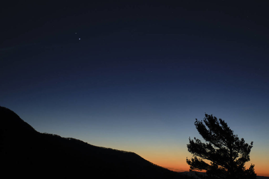 """In this Sunday, Dec. 13, 2020 photo made available by NASA, Saturn, top, and Jupiter, below, are seen after sunset from Shenandoah National Park in Luray, Va. The two planets are drawing closer to each other in the sky as they head towards a """"great conjunction"""" on Monday, Dec. 21, where the two giant planets will appear a tenth of a degree apart. (Bill Ingalls/NASA via AP)"""