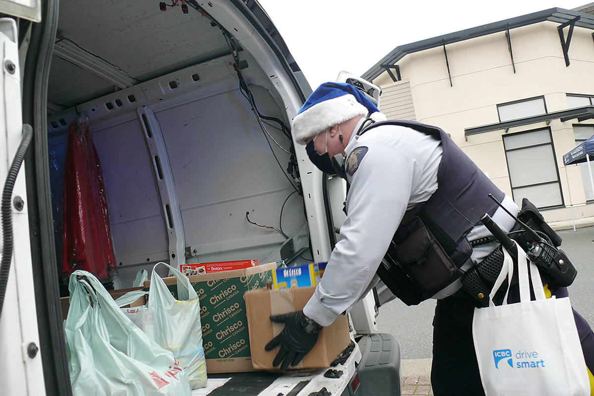 Langley RCMP Const. Phil Colter loads the big van at the Saturday, Dec. 19 Pack the Police Car event held at Willoughby Town Centre to help the Langley Food Bank. (Dan Ferguson/Langley Advance Times) (Dan Ferguson/Langley Advance Times)