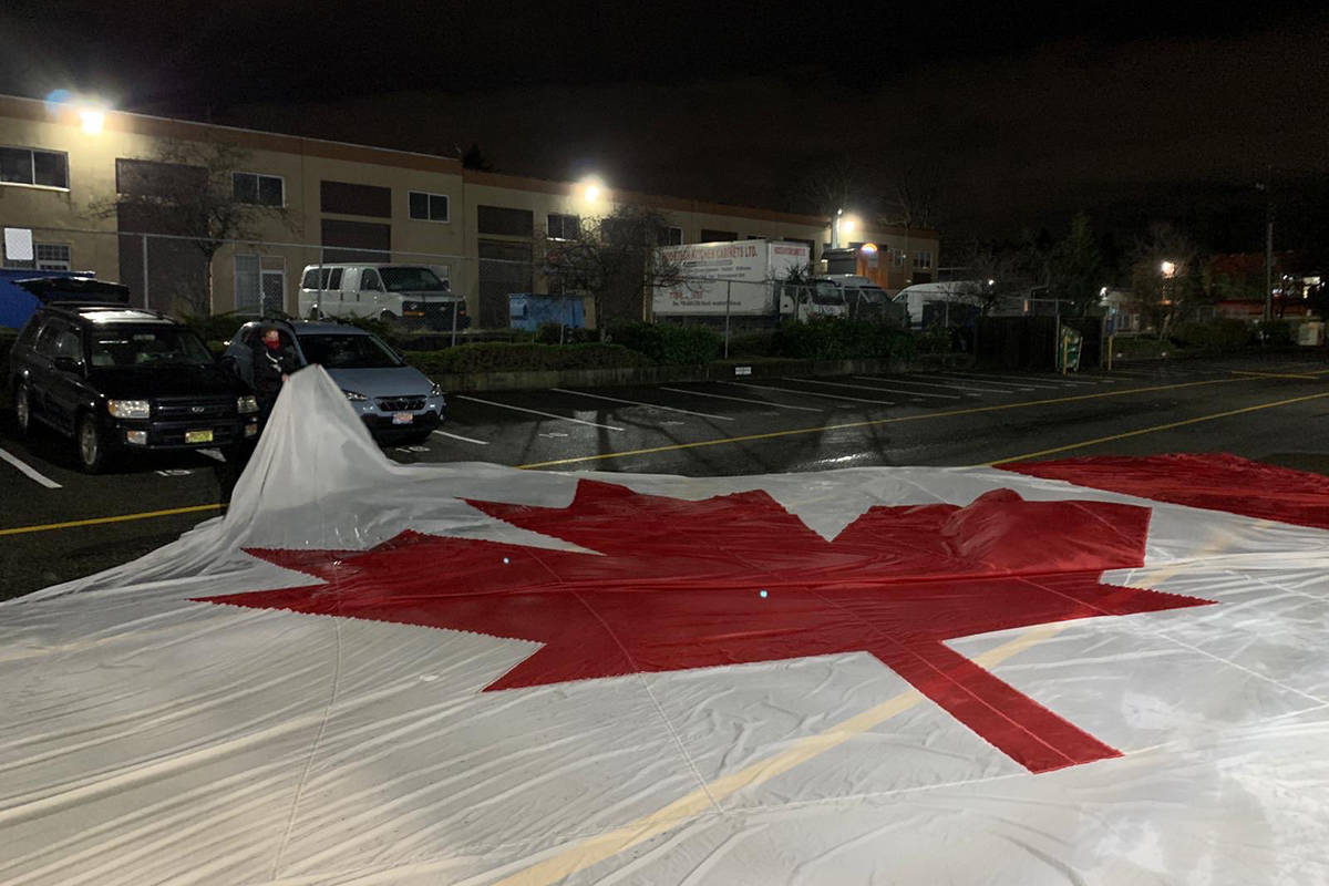 Guildford's giant Canadian flag in a parking lot after it fell from its pole, on 104th Avenue, early Saturday. (Photo: twitter.com/PreventCrimes)
