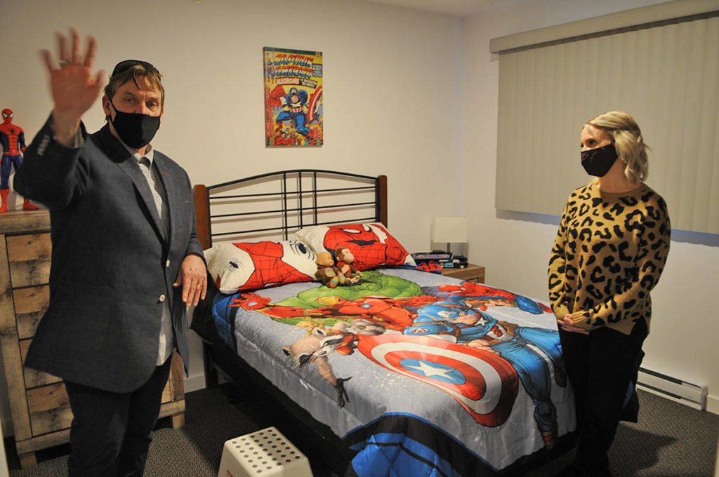 Les Talvio and Alyssa Vlaanderen show off the superhero-themed room of one of the two-bedroom units at The Switchback, a supportive housing building for youth on Dec. 18, 2020. (Jenna Hauck/ Chilliwack Progress)