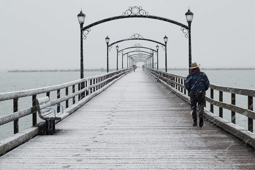 A man walks on the snow-covered White Rock Pier Monday morning. (Aaron Hinks photo)
