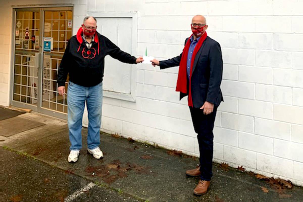 Aldergrove legion branch #265 president Doug Hadley accepts a donation from Langley MP Tako van Popta. (Special to The Star)