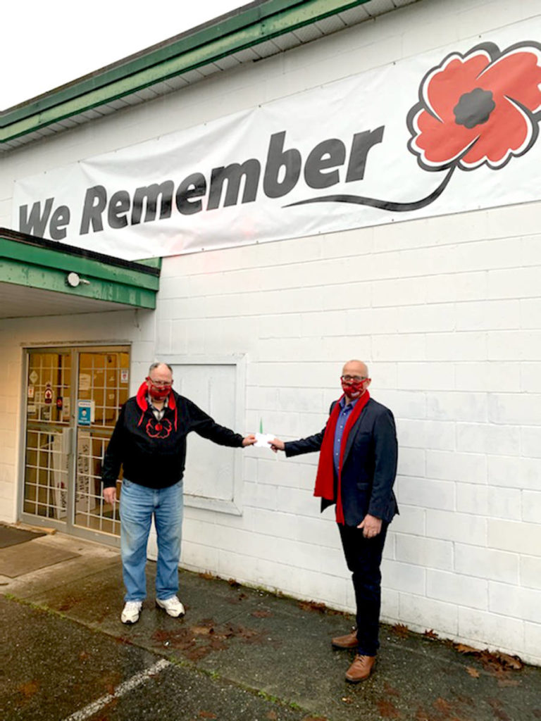 Aldergrove legion branch #265 president Doug Hadley accepts a donation from Langley MP Tako van Popta. (Special to The Star)