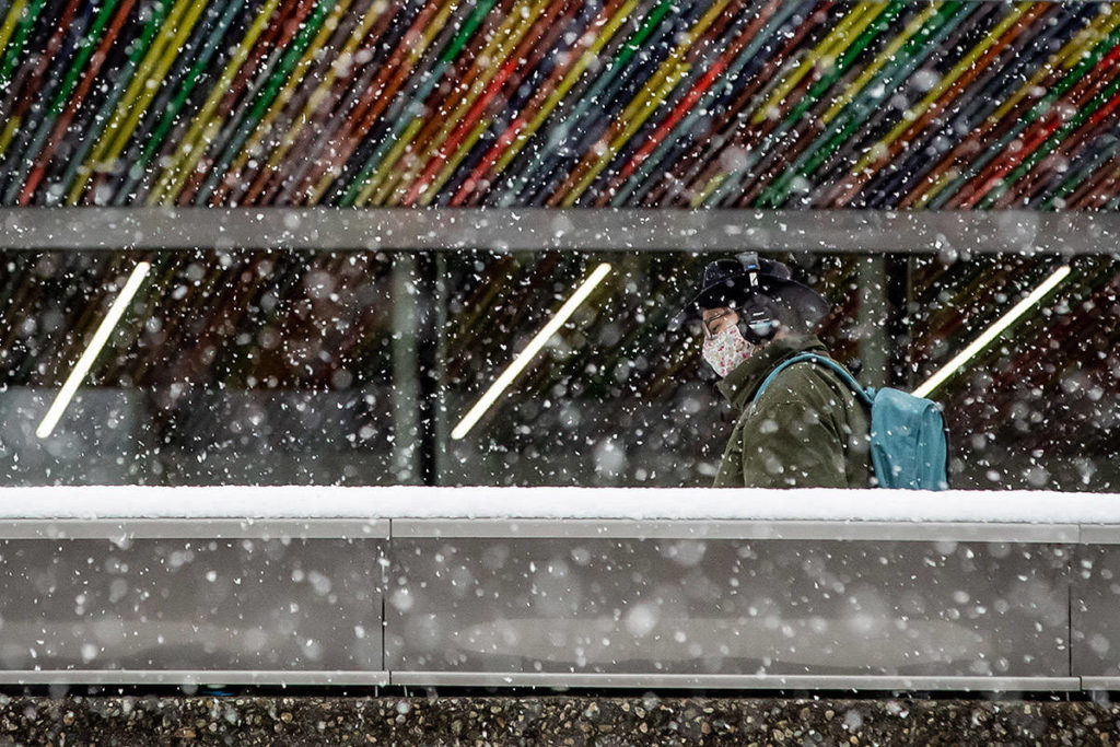 Heavy snow falls as a man wearing a face mask to curb the spread of COVID-19 walks on the Simon Fraser University campus, in Burnaby, B.C., on Monday, December 21, 2020. Environment Canada issued a snowfall warning on the first day of winter with up to 5cm of snow expected for Metro Vancouver and up to 20cm for other areas of the province. THE CANADIAN PRESS/Darryl Dyck