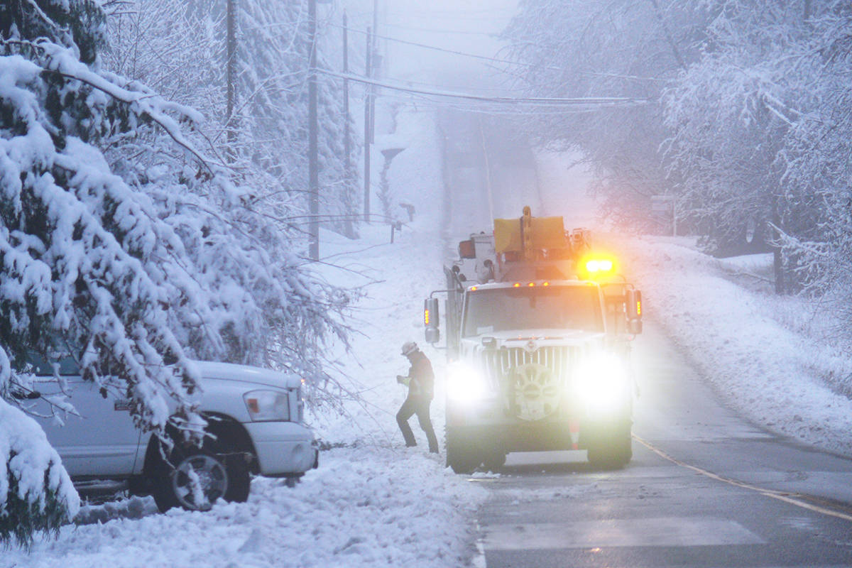 A crew truck was looking for downed power lines on 240 Street in Langley's Otter area on Tuesday morning, Dec. 22. A winter storm that dumped wet snow on Langley caused multiple electrical outages. (Dan Ferguson/Langley Advance Times)