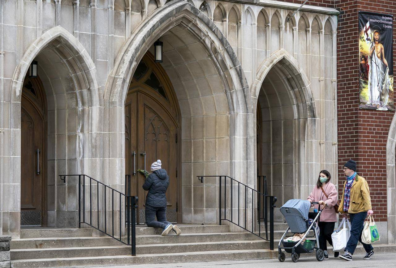 A woman prays on the steps outside St. Casimir Church in Toronto on Friday, May 1, 2020. THE CANADIAN PRESS/Frank Gunn