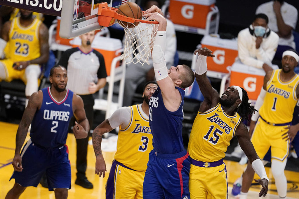 Los Angeles Clippers center Ivica Zubac, center, dunks past Los Angeles Lakers forward Montrezl Harrell (15) during the second half of an NBA basketball game Tuesday, Dec. 22, 2020, in Los Angeles. (AP Photo/Marcio Jose Sanchez)