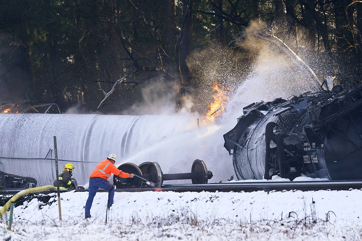 A firefighter sprays foam on a burning, derailed train car Tuesday, Dec. 22, 2020, in Custer, Wash. Officials say seven train cars carrying crude oil derailed and five caught fire north of Seattle and close to the Canadian border. Whatcom County officials said the derailment occurred in the downtown Custer area, where streets were closed and evacuations ordered during a large fire response. (AP Photo/Elaine Thompson)