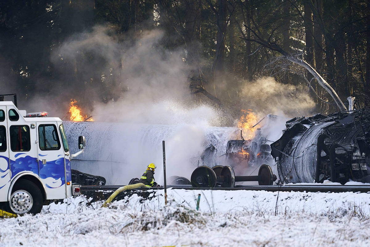 A firefighter sprays foam on burning, derailed train cars Tuesday, Dec. 22, 2020, in Custer, Wash. Officials say seven train cars carrying crude oil derailed and five caught fire north of Seattle and close to the Canadian border. Whatcom County officials said the derailment occurred in the downtown Custer area, where streets were closed and evacuations ordered during a large fire response. (AP Photo/Elaine Thompson)