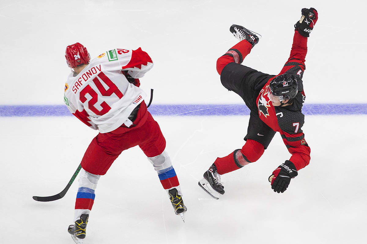 Canada's Kirby Dach (7) is checked by Russia's Ilya Safonov (24) during third period IIHF World Junior Hockey Championship pre-competition action in Edmonton on Wednesday, December 23, 2020. THE CANADIAN PRESS/Jason Franson