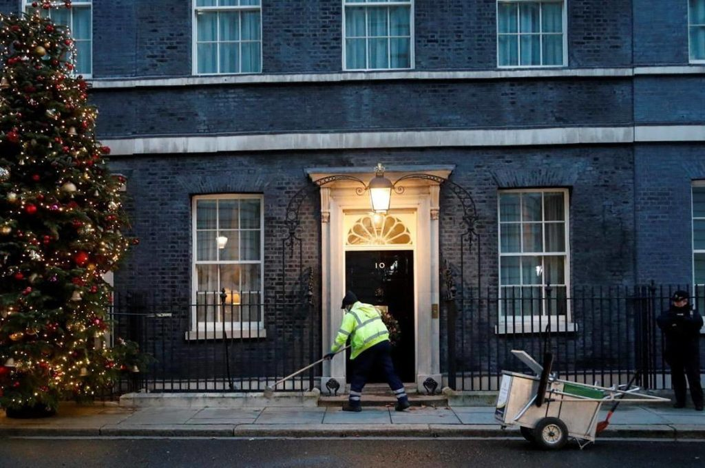A cleaner sweeps the pavement front of 10 Downing Street in London, Thursday, Dec. 24, 2020. Negotiators from the European Union and Britain worked through the night and right into Christmas Eve to put the finishing touches on a trade deal that should avert a chaotic economic break between the two sides on New Year's Day. (AP Photo/Frank Augstein)