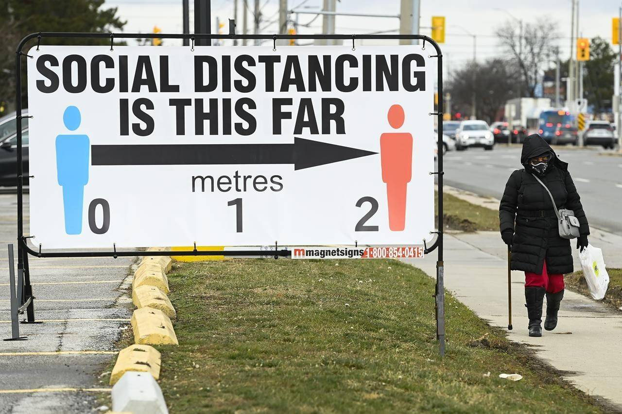 A person walks past a COVID-19 restrictions sign during in Mississauga, Ont., on Tuesday, December 22, 2020. Ontario is reporting a new daily record for COVID-19 infections as Prime Minister Justin Trudeau acknowledges this Christmas won't be the one Canadians had hoped for. THE CANADIAN PRESS/Nathan Denette